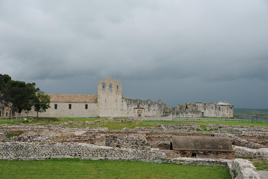 Vor einem grauen Himmel heben sich die weißen der Mauern einer Ruine ab. Vorne der archäologische Park von Venosa.