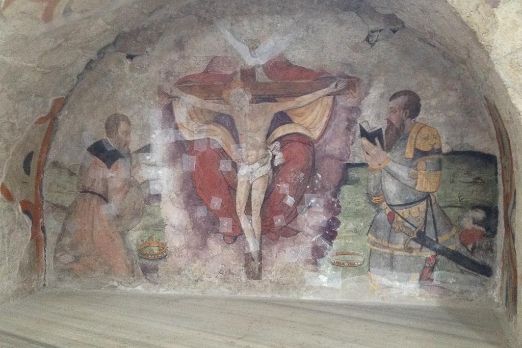 Das Grab Robert Guiscard in der Kirche Santissima Trinita in Venosa in einer Wandnische mit Bild einer Kreuzigung.