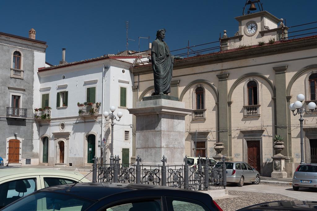 Auf einem Marmorsockel steht die Statue von Horaz, er trägt eine Toga und hält eine Schriftrolle in der Hand.