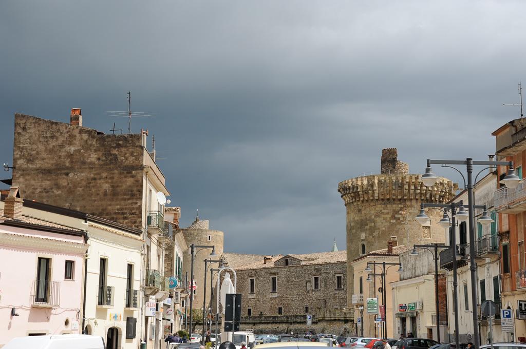 Eine breite Straße führ auf das Zentrum von Venosa zu. Rechts erhebt sich ein Turm des Kastells.