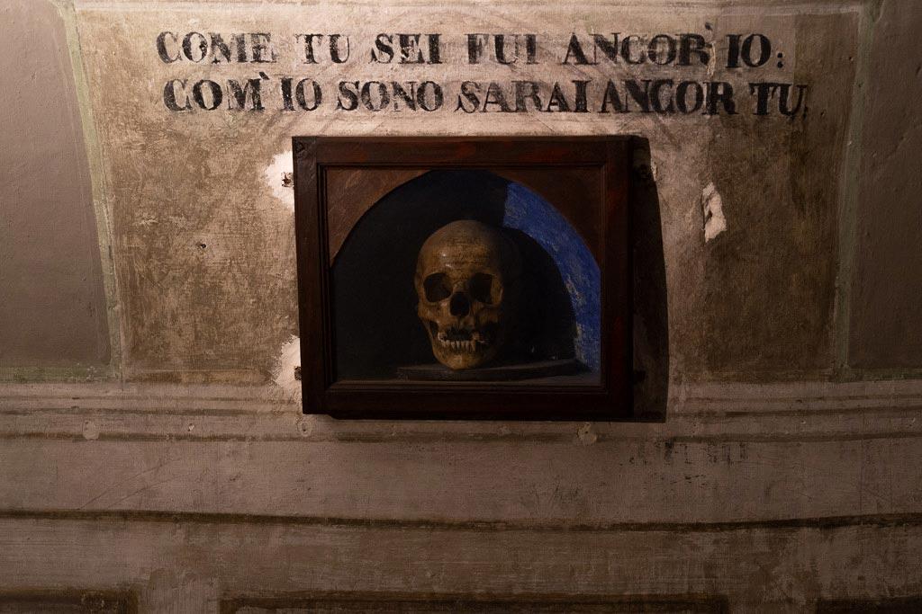 Ein Totenkopf in einem unterirdischen Korridor mit einer Schrift darüber.