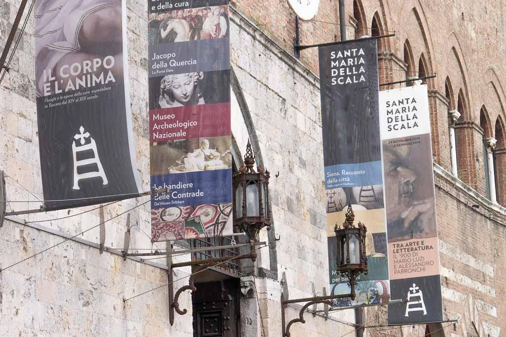 Fahnen weisen auf die Siena Sehenswürdigkeit Santa Maria della Scala hin.